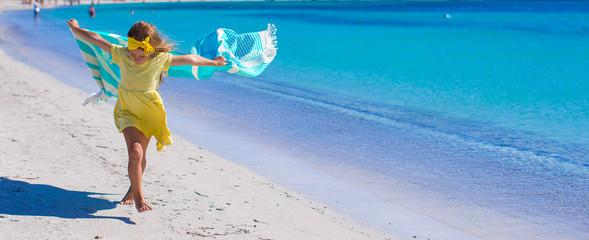 Little cute girl have fun with beach towel