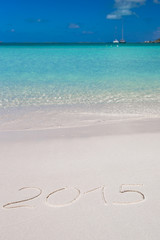 2015 written on tropical beach white sand with xmas hat