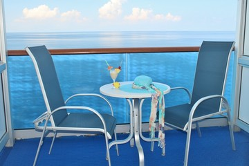 Cruise ship balcony chairs, table and tropical drink