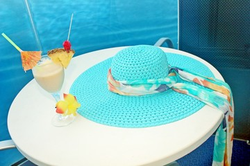 Pina Colada and a summer hat laying on a table with the ocean in