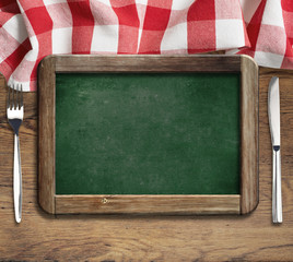 Menu blackboard on table with knife and fork