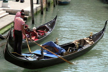 Gondoliers with tourists on canal, Venice, Italy