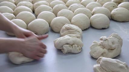 Baker kneading dough in a bakery