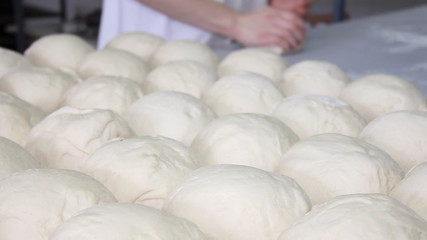 Baker kneading dough in a bakery