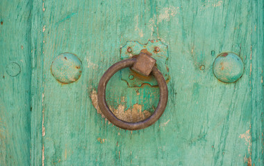 Front view of old doorknocker and green painted wooden door