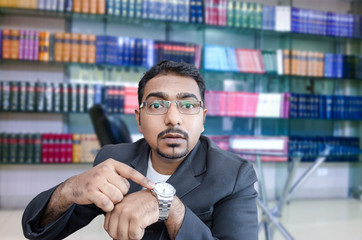 indian businessman with french beard pointing at wrist watch