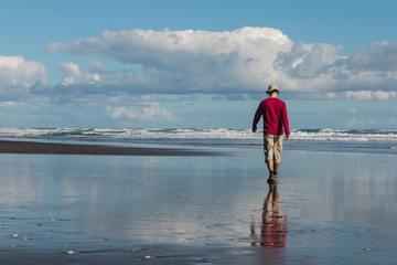 man walking on Karekare beach in New Zealand