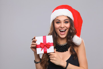 Woman in Santa hat holding gifts, isolated on gray background