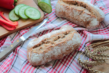 Homemade bread rolls with knife and fresh vegetables