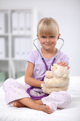 Little girl is examining her teddy bear using stethoscope