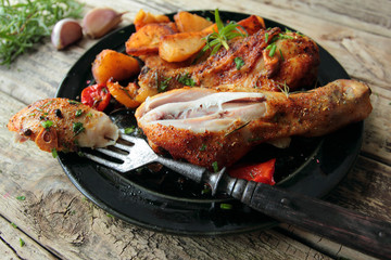 Plate with roasted chicken legs with herbs