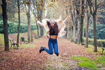 Jumping young woman outdoors in a park in autumn.