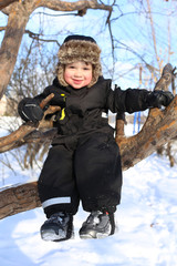 happy 2 year toddler sitting on tree in winter
