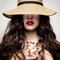 Glamorous portrait of a brunette in a straw hat.