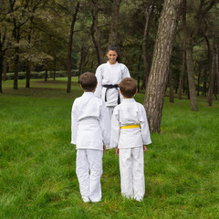 Two kids and master practicing judo outdoors in a park.