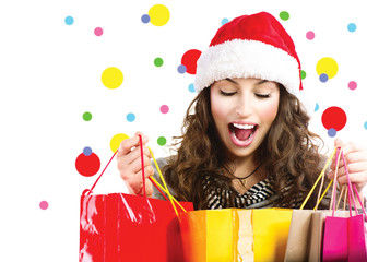 Christmas sales. Surprised woman with colorful shopping bags