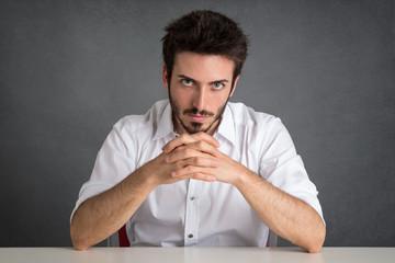 Confident man portrait over dark grunge background.