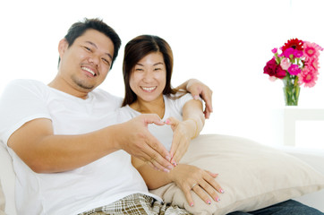 Asian couple relaxed at home. Focus on the hands