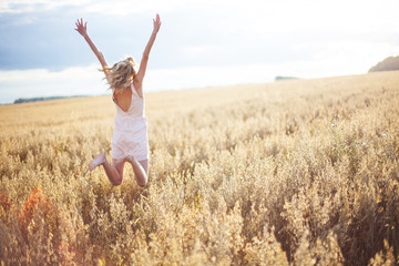 Woman in Wheat Field With Arms Outstretched