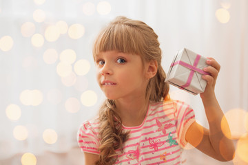 Cute little girl holding a gart box at home. Holiday lights arou