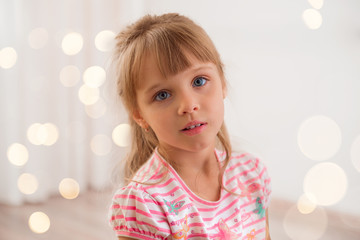 Cute little girl at home. Holiday lights around.