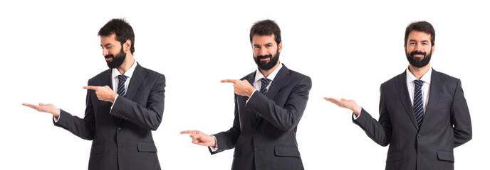 Businessman pointing to the lateral over white background