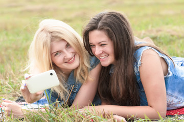 Blonde and brunette girls making selfie with phone