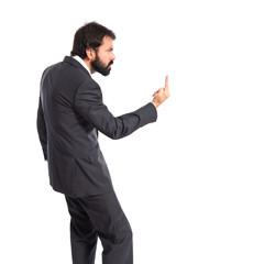 Businessman making horn gesture over white background