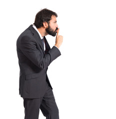 Businessman with costume making silence gesture