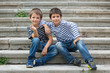 Two brothers portrait having fun sit on stairs outdoors.