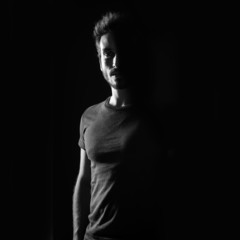 Dark shadow portrait of confident young man wearing shirt agains