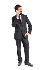 Businessman talking to mobile over white background