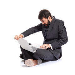 Angry businessman with laptop over white background