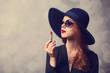 Style redhead women with sunglasses and lipstick.