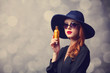 Style redhead girl in a hat holding perfume