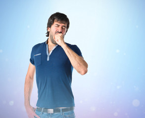 Man yawning over isolated blue background