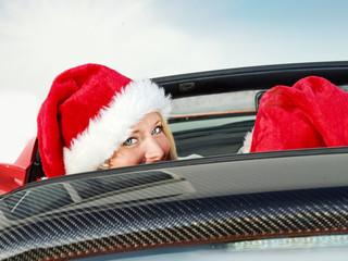 Miss Santa driving a red roadstar