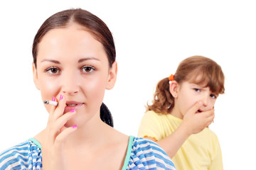 girl smoking cigarette and little girl coughs