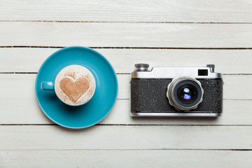 Retro camera and cup of coffee on wooden table.