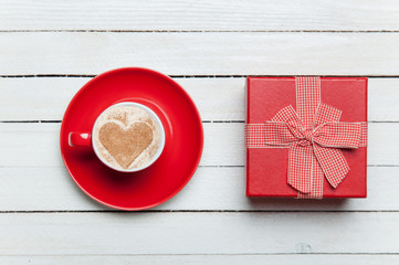 Cup of coffee and gift on wooden table.