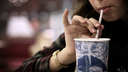 Fast food restaurant : girl drinking cold beverage with straw
