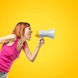 Redhead girl shouting with a megaphone over yellow background