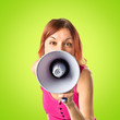 Redhead girl shouting with a megaphone over green background