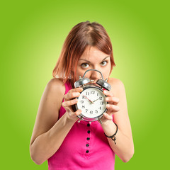 Serious redhead girl holding a clock over green background