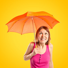 Girl holding an umbrella over yellow background