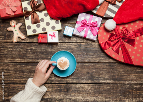 canvas print picture Female holding cup of coffee on wooden table near christmas gift
