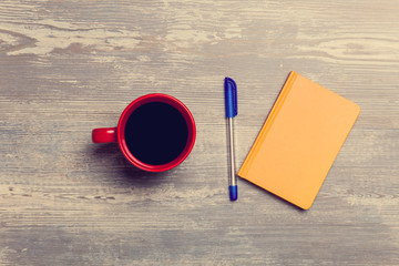 Coffee cup and notebook on a table.