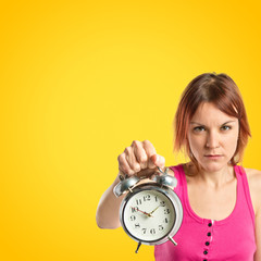 Serious redhead girl holding a clock over yellow background