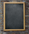 Aged menu blackboard hanging on brick wall