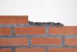 Construyendo un muro de ladrillos con cemento.
